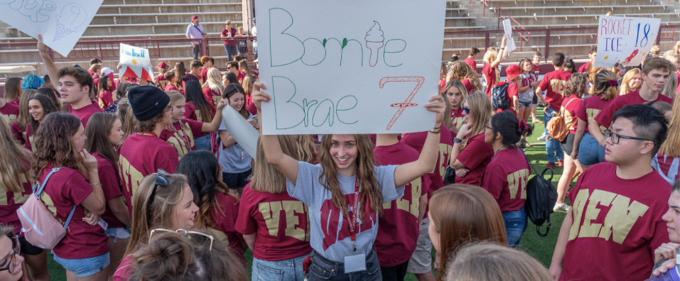 Discoveries Orientation Leader holding up her Orientation Group Sign in a crowd of new students.