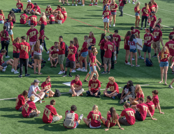 A orientation group sitting together in a circle on the lacrosse field.