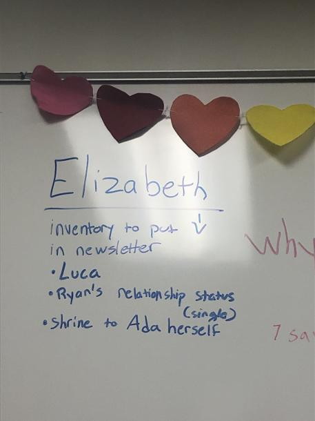A picture of the whiteboard in the OUTspoken office. Written in blue marker is: Elizabeth. Inventory to put in newsletter: Luca, Ryan's relationship status (single), shrine to Ada herself.