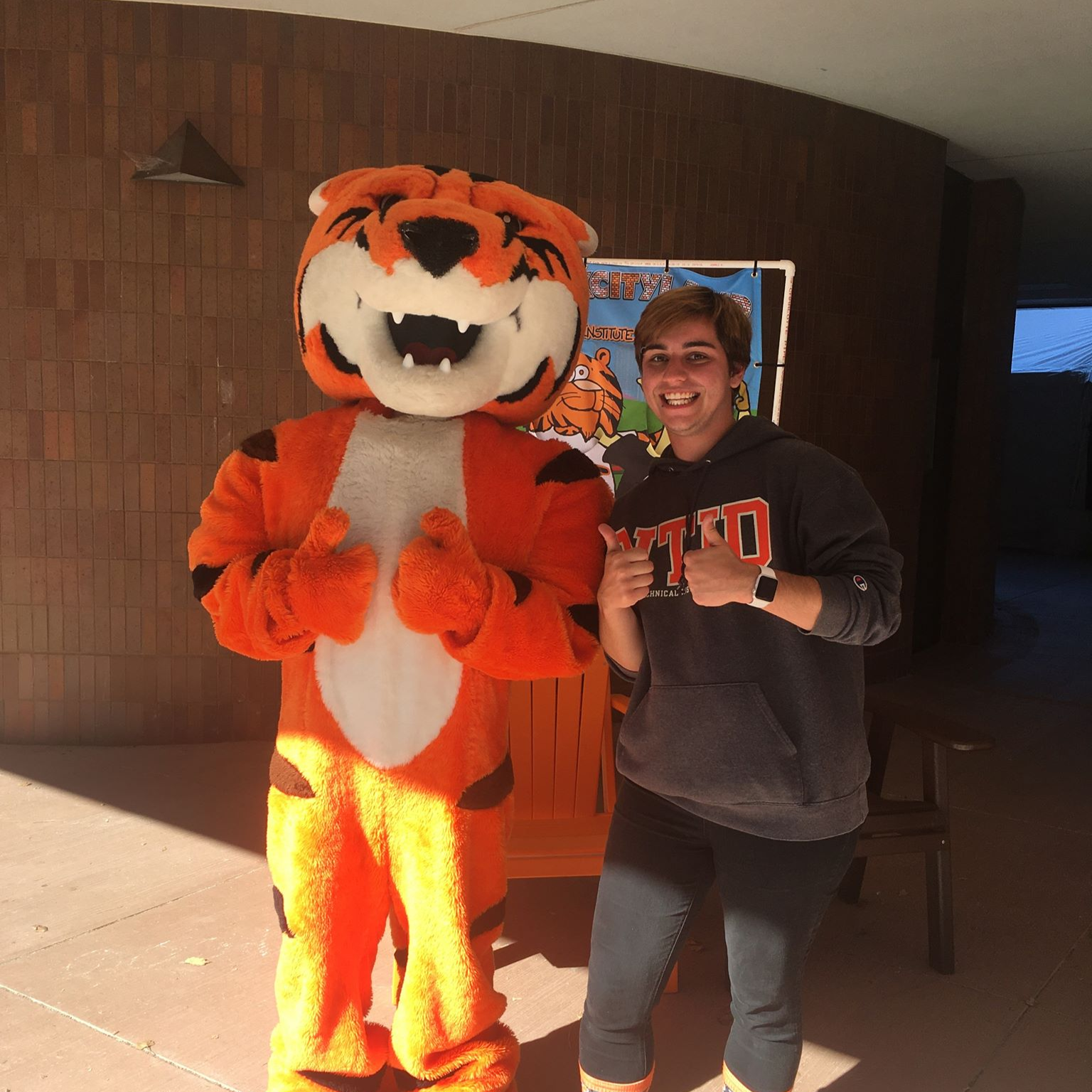 Ryan standing next to the Ritchie mascot in front of the liberal arts hall, both givng the camera two thumbs up.